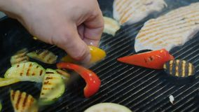 Fried vegetables, chicken fillet, Cooking meat and vegetables on the grill. Hand, using a spatula to turn the meat into. A barbecue. Sausages, chicken, sweet stock video footage