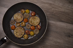 Fried vegetables on frying pan Stock Photos