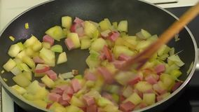 Fried vegetables,ham in a pan stock footage