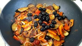 Fried vegetables: onions, carrots, peppers, decorated with black olives. Vegetable stew in a pan. The process of stewing vegetable