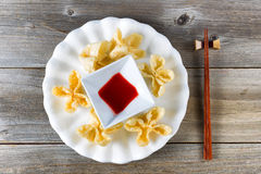 Fried wanton shells and sweet dipping sauce in white bowl on rus Stock Photography