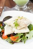 Fried white fish fillet with salad of tomatoes, arugula, herbs Stock Photo