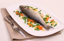 Fried whole moronidae fish, vegetables and lemon Stock Images