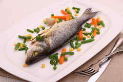 Fried whole sea bass with vegetables and lemon Royalty Free Stock Photo