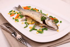 Fried whole sea bass with vegetables, lemon Stock Image