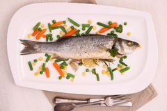 Fried whole sea bass with vegetables and lemon Stock Photos