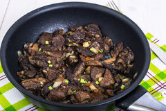 Fried wild mushrooms with onion in pan Stock Photo