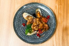 Fried wings with mussels in a black plate royalty free stock photography