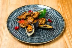 Fried wings with mussels in a black plate royalty free stock photos