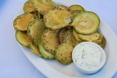 Fried zucchini chips with tzatziki Greek tavern plate. Floured zucchini are a dish commonly served at Greek tavernas, with a tzatziki sauce made of yogurt royalty free stock photos