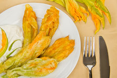 Fried zucchini flowers with cutlery. Top view Stock Image