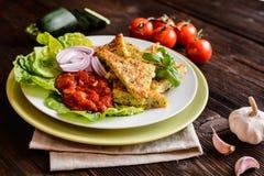 Fried zucchini pancakes with tomato salsa Stock Photo