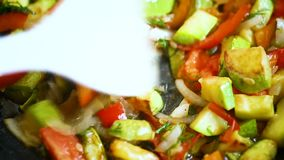 Fried zucchini with red pepper, onions, tomatoes and other vegetables stock footage