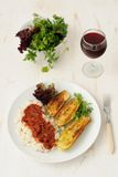 Fried zucchini with rice and sause, fresh herbs and a glass of wine. On white background Stock Image