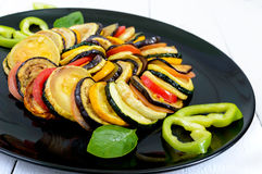 Fried zucchini slices, eggplant, tomato on a black plate on a white background. Stock Photography