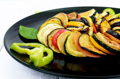 Fried zucchini slices, eggplant, tomato on a black plate on a white background. Stock Photos