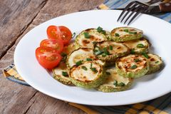 Fried zucchini on a white plate with fresh tomatoes. Stock Image