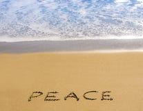 Frieden geschrieben in goldenen Sand mit Brandung Stockfoto
