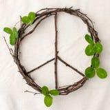 Friedenszeichen, Symbol des natürlichen Materials - Blumen, Blätter, hölzerne Stöcke auf Gewebeweißhintergrund Stockfoto
