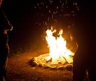 Frieds autour d'un camp de feu la nuit Photographie stock libre de droits