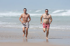 Frieds jogging on the beach Stock Images