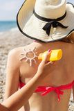 Friend applying sunscreen lotion over tan woman Royalty Free Stock Photography