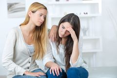 Friend comforting sorrowful young female teenager. Young royalty free stock photo