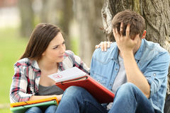 Friend comforting to a sad student with failed exam. Sitting on the grass in a park Stock Photography