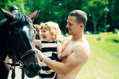 Friend, companion, friendship. Girl with men pet horse on sunny day. Child with muscular macho smile to animal. Equine therapy, recreation concept. Happy stock photography