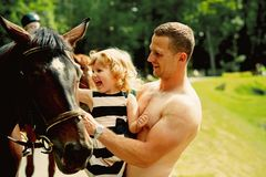 Friend, companion, friendship. Girl with men pet horse on sunny day. Child with muscular macho smile to animal. Equine therapy, recreation concept. Happy stock image
