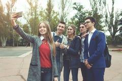 Friend company makes selfi. A friend company makes selfi on a smartphone Stock Photography