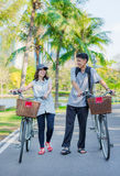 A friend couple are walking and chatting with bicy Stock Images