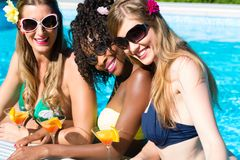 Friend drinking cocktails in swimming pool bar. Three women friends drinking cocktails in swimming pool bar, African and Caucasian girls stock images