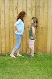 Friend fighting faces. Two young female children making mad faces at each other against a tall fence outdoors Royalty Free Stock Photography