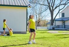 Friend girls teens playing football soccer in a park stock photography