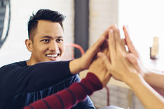 Friend giving high five at cafe Stock Photos