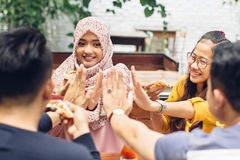 Friend giving high five at cafe Stock Photo