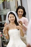 Friend helping bride. African-American friend holding Asian bride's veil Stock Photography