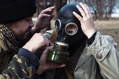 A friend helps his buddy to take on the gas mask for the mission Stock Photography