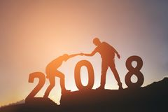 Friend hiking help each other silhouette in 2018 new year on mou Royalty Free Stock Image