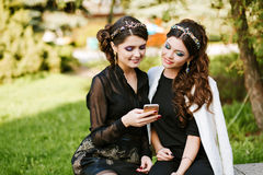 Friend look at the phone and discuss something. Laughing and smiling, going crazy, having fun. Young stylish woman at Royalty Free Stock Images