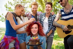 Friend put to birthday hat on head of reveler. Female friend put birthday hat on head of sweet reveler Stock Images