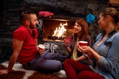 Friend`s relaxation after skiing in front of fireplace. At home royalty free stock photography