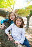 Friend sister girls resting on tree trunk nature Stock Photo