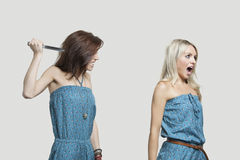 Friend stabbing young woman in similar jump suits from behind. Friend stabbing young women in similar jump suits from behind Royalty Free Stock Image