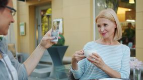 Friend taking photo of beautiful mature blonde holding coffee cup in street cafe. Friend woman is taking photo of beautiful mature blonde holding coffee cup in stock video footage