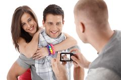 Friend taking photo of happy couple. Smiling and hugging, isolated on white Royalty Free Stock Photos