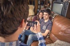 Friend taking photos to teenage couple on a sofa stock image
