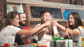 Friend Tells a Toast. Bearded fair-haired man telling a toast to happy young woman while everybody lifting glasses with champagne, slowmotion on lovely relaxing stock footage