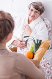 Friend visiting woman. Friend with shopping visiting older women lying in hospital bed Stock Photography